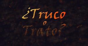Truco o Trato et x28 ; Tour ou Treat& x29 ; Texte espagnol se dissolvant dans la poussière du fond Photos libres de droits
