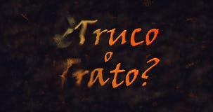 Truco o Trato y x28; Truco o Treat& x29; Texto español que disuelve en el polvo de la izquierda Imagen de archivo