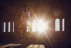 Trucos de BMX en un rayo solar interior Fotos de archivo libres de regalías