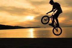 Trucos del motorista de Bmx contra una puesta del sol hermosa Foto de archivo libre de regalías