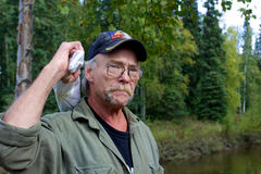 True Alaskan man in 60s. Fairbanks, Alaska, United States - September 5, 2014: Typical man from Alaska in his late 50s with beard, glasses and a baseball cap who royalty free stock photography