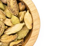 True cardamom pod isolated on white. Closeup of lot of whole true cardamom pod in a wooden bowl flatlay isolated on white background stock image