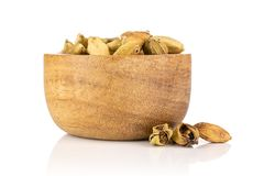 True cardamom pod isolated on white. Lot of whole true cardamom pod near and in a wooden bowl isolated on white background royalty free stock image