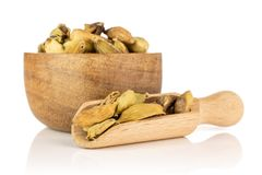 True cardamom pod isolated on white. Lot of whole true cardamom pod in a wooden bowl with wooden scoop isolated on white background royalty free stock images