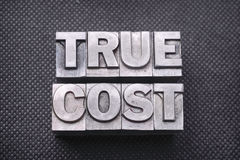 True cost bm. True cost phrase made from metallic letterpress blocks on black perforated surface Stock Photos