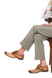 True elegance. Legs of man in grey pants and stylish shoes sitting cross-legged on chair Royalty Free Stock Photo