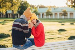 True feelings and romantisism concept. Adorable young woman in knitted yellow hat and red warm sweater warms her hands in boyfrien royalty free stock image