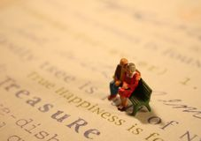 True Happiness couple(concept). Concept of an older couple with true happiness. Two miniature figurines are on a bench surrounded by words such as True Happiness Royalty Free Stock Image