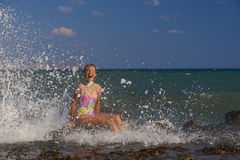True happiness. A young girl is enjoying the splashing droplets Stock Image