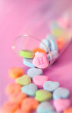 True Love on a candy heart. Valentine's Day Candy Hearts spill from a champagne glass. Soft focus. Heart in focus says True Love Stock Photos