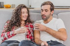 True love. Cheerful romantic couple sitting on the couch in a cozy room and smiling. stock photos