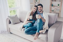 True love. Cheerful romantic couple is sitting on sofa under cozy plaid and smiling. They are drinking tea, wearing casual clothe stock images