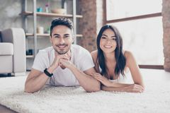 True love. Happy beautiful married latino mulatto couple is chilling out lying on the carpet at the floor at home stock photos