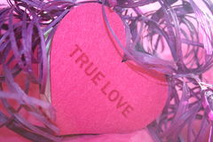 True Love Heart. Pink felt heart with the words True Love surrounded by curls of purple raffia ribbon stock images