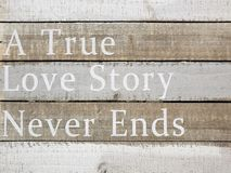 A true love story never ends. Sentence a true love story never ends print on wood stock photography