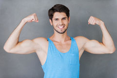 True masculinity. Handsome young muscular man showing his perfect biceps while standing against grey background Royalty Free Stock Photography