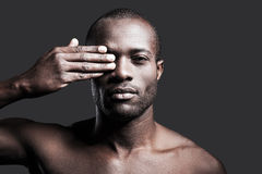 True masculinity. Portrait of young shirtless African man covering one eye with hand and looking at camera while standing against grey background Stock Photos