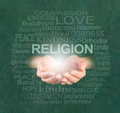 The only true religion is KINDNESS. Female cupped hands with a ball of light and the word RELIGION floating above, surrounded by a religion word cloud on a royalty free stock photo
