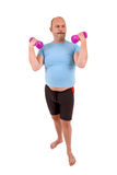 True sportsman. Overweight man with beer belly and very light hand weights Stock Images