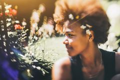 Black girl in park, tilt-shift shooting. True tilt-shift art portrait of attractive young African American female in city park with chamomiles woven into her royalty free stock photos