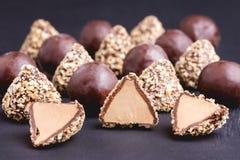 Trufa fresca hecha en casa con cierre horizontal del fondo negro de los caramelos de chocolate de la mantequilla del cacao y de c Imagenes de archivo