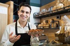 Trufas de chocolate de oferecimento do pasteleiro masculino foto de stock royalty free