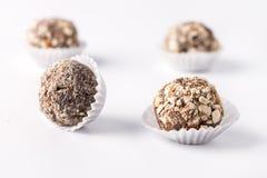Trufas de chocolate decoradas com as porcas no grupo caseiro saboroso bonito dos doces do fundo branco de doces fotografia de stock