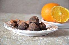 Trufas de chocolate del caramelo en una placa, con canela y anís En una tabla mantenida con las naranjas Fotos de archivo