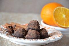 Trufas de chocolate del caramelo en una placa, con canela y anís En una tabla mantenida con las naranjas Imagen de archivo libre de regalías