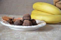 Trufas de chocolate del caramelo en una placa, con canela y anís En una tabla mantenida con los plátanos Fotos de archivo libres de regalías