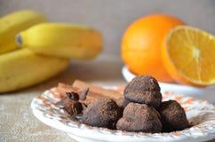 Trufas de chocolate del caramelo en una placa, con canela y anís En una tabla mantenida con los plátanos y las naranjas Foto de archivo
