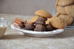 Trufas de chocolate del caramelo en una placa, con canela y anís En una tabla mantenida, taza de cofee, galleta Imágenes de archivo libres de regalías