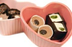 Trufas de chocolate en platos en forma de corazón Fotografía de archivo libre de regalías