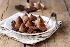 Trufas de chocolate hechas en casa con el polvo de cacao en un caramelo sabroso fondo de madera blanco de la placa del viejo hori fotos de archivo