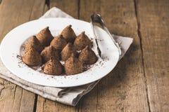 Trufas de chocolate hechas en casa con el polvo de cacao en un espacio sabroso de la copia del caramelo fondo de madera blanco de fotos de archivo libres de regalías
