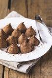 Trufas de chocolate hechas en casa con el polvo de cacao en una vertical sabrosa del caramelo fondo de madera blanco de la placa  fotografía de archivo