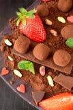 Trufas de chocolate rodeadas por las fresas y la menta imágenes de archivo libres de regalías