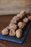 Truffes de chocolat en cacao arrosé Sur le panneau d'ardoise sur le fond en bois L'espace libre pour la conception Photos stock