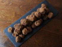 Truffes de chocolat en cacao arrosé Sur le panneau d'ardoise sur le fond en bois L'espace libre pour la conception Images stock