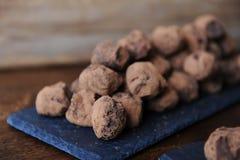 Truffes de chocolat en cacao arrosé Sur le panneau d'ardoise sur le fond en bois L'espace libre pour la conception Photographie stock