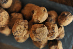 Truffes de chocolat en cacao arrosé Sur le panneau d'ardoise sur le fond en bois Plan rapproché, texture Image libre de droits