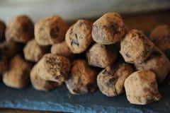 Truffes de chocolat en cacao arrosé Sur le panneau d'ardoise sur le fond en bois Plan rapproché, texture Photographie stock libre de droits