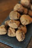 Truffes de chocolat en cacao arrosé Sur le panneau d'ardoise sur le fond en bois Plan rapproché, texture Photographie stock