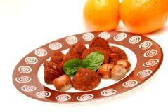 Truffes, noisettes, lames en bon état et oranges Images stock