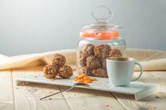 Truffle balls with orange chocolate on the saucer next to the jar of candy and a Cup of coffee. The concept of delicious desserts gifts Stock Image