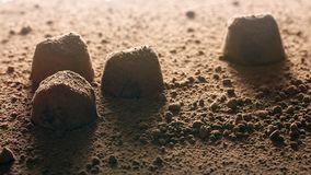 Truffle candies and cocoa powder close-up in hard backlight, similar to the surface of Mars. Background image for Valentine`s Day or for a box of chocolates stock image