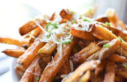 Truffle Parmesan Fries. Fresh cut potatoes, tossed with white truffle oil, Parmesan and chives, served with peppercorn garlic sauce royalty free stock image