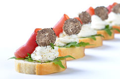 Truffle tidbits. Yummy morsels with spiced cream cheese, ham, rucola and Italian black truffles Royalty Free Stock Photo