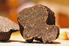 Truffles. Black truffles (tuber melanosporum) on a table stock image