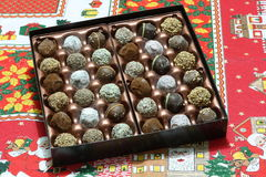 Box of Chocolate Christmas Truffles. Box of chocolate candies or truffles on Christmas cloth Stock Images